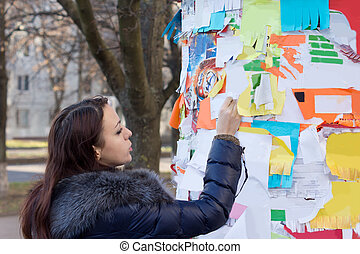 Woman tearing off a contact number on a notice - Woman...