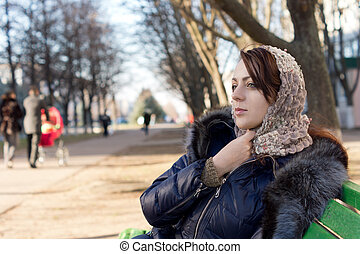 Lonely young woman sitting on a park bench clasping a scarf...