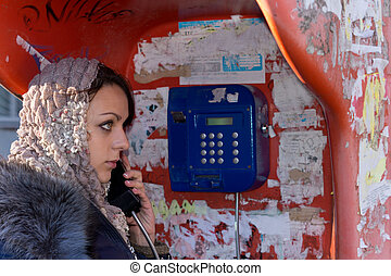 Beautiful young woman using a public payphone