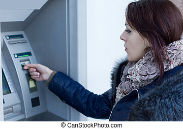Woman retrieving her bank card at the ATM waiting for it to...