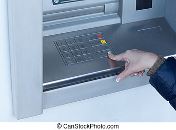 Woman completing a transaction on an ATM outside a bank as...