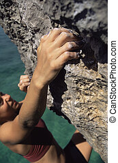 Woman climbing rocks in swimwear by ocean selective focus