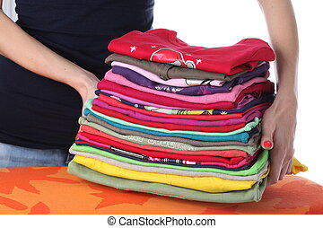 Laundry on ironing board - Woman raising up coloured pile of...