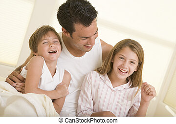 Man with two young children sitting in bed smiling