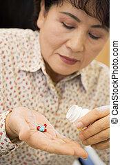 mujer, toma, píldoras
