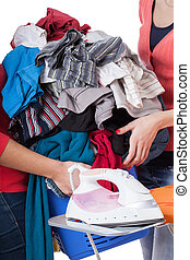 Heap of laundry - Women passing each other a heap of...