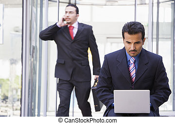 Businessman outdoors in front of building using laptop with businessman in background on cellular phone (high key/selective focus)