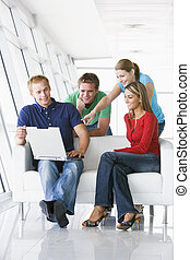 Four people in lobby pointing at laptop smiling