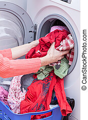 Preparing washing - Woman's hands putting clothes into...