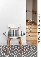 Chair with cushion in a room with staircase - Chair...