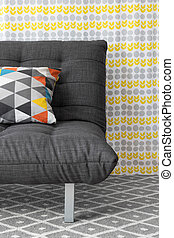 Sofa with colorful cushion, on bright floral background.