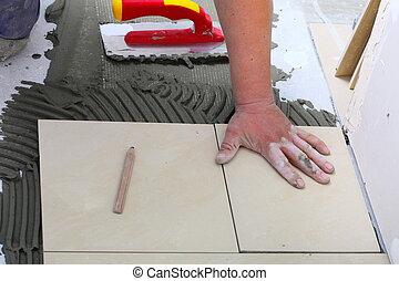 Construction worker is tiling at home, tile floor adhesive -...