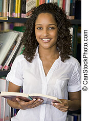 Woman in library holding book