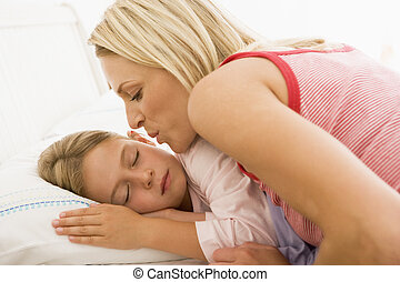 Woman waking young girl in bed with a kiss