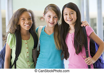 Three students standing outside school together smiling...