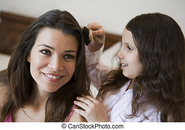 Young girl brushing woman\'s hair on bed in bedroom smiling (selective focus)
