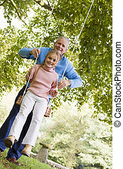 Grandfather pushing granddaughter on swing and smiling...