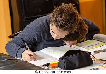 Student girl at home writing with a pencil