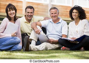Adulto, estudiantes, césped, escuela, cuadernos