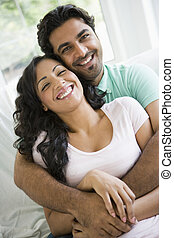 Couple in living room embracing and smiling high key