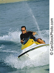 Man jet skiing and smiling (selective focus)