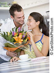 Young man giving a bouquet of flowers to a young girl...