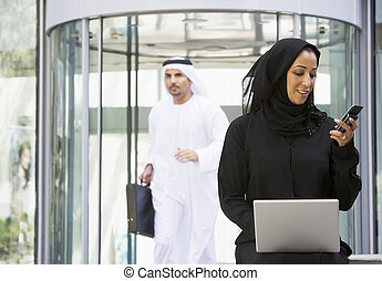 Businesswoman sitting outdoors by building with laptop...
