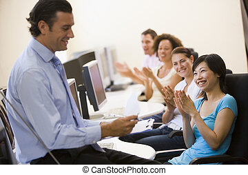 Man with clipboard giving lecture in applauding computer...