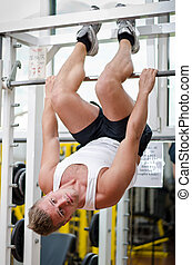Young man in gym hanging upside-down to exercise abs