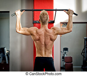 Athletic young man hanging from gym equipment - Blond,...