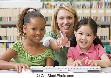 Two students in class at computer keyboard with teacher