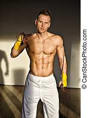 Shirtless muscular young man standing with jumping rope in...