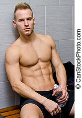 Shirtless handsome male athlete resting on bench, water...