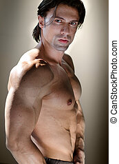 Shirtless muscular man on neutral background looking at...