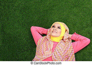 Young muslim girl wearing hijab lying on grass and looking up