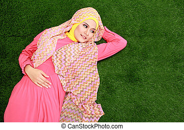 Young muslim girl wearing hijab lying on grass - Portrait of...