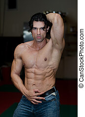 Handsome shirtless muscular man with jeans in gym -...