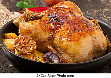 Baked whole chicken with potatoes, garlic and onion