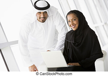 Two people indoors with laptop smiling high keyselective...
