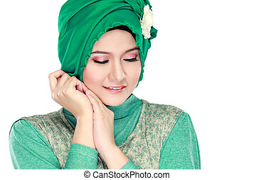Fashion portrait of young beautiful muslim woman with green...