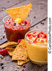 Salsa- and Cheese Sauce on wooden background - Salsa- and...