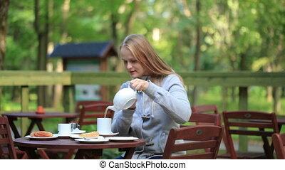 Young woman enjoying a pot of tea