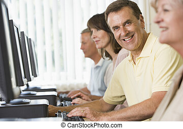 Four people sitting at computer terminals (selective...