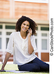 Woman on lawn of school using cellular phone