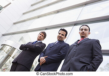 Three businessmen standing outdoors by building high...