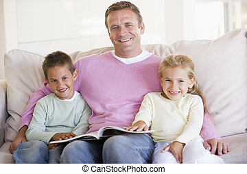 Man and two children sitting in living room reading book and...
