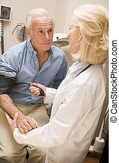Doctor Measuring Mans Blood Pressure
