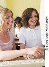 Student and teacher at computer terminal with student in...