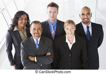 Group of co-workers standing in office space smiling high...