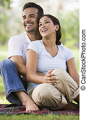 Couple sitting outdoors in park smiling selective focus